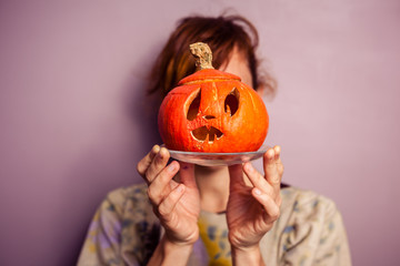 Young woman with scary pumpkin in front of her face