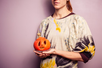 Young woman holding a scary jack-o-lantern