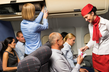 Air stewardess check ticket airplane cabin smiling