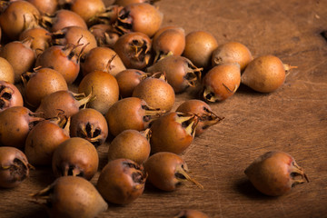 Medlar Fruits on Wooden Board