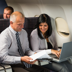 Businesspeople working on computer flight airplane