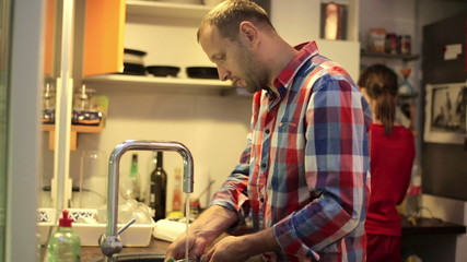 Young man doing dishes after diner in the kitchen at home