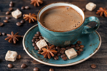 Сoffee cup with spices on dark wooden background