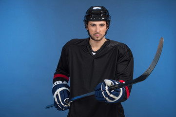 Handsome hockey player standing isolated on blue background