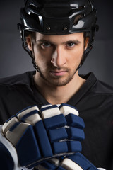 Portrait of handsome hockey player in black helmet.