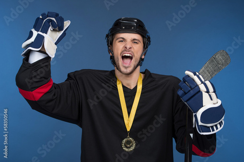 Hockey player is celebrating his victory with happy emotion.