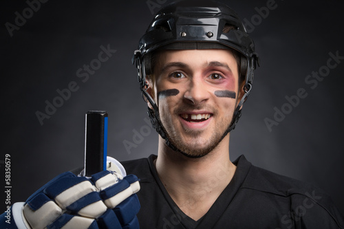 Leinwandbild Motiv Funny hockey player smiling with one tooth missing.