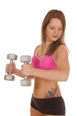 Woman pink bra fitness hammer curl look down