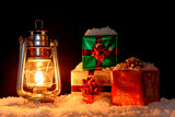 Christmas gifts and oil lamp on snow