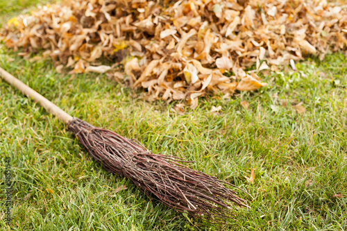 Autumn clearing - besom and a pile of leaves