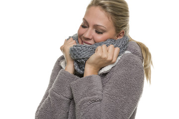 Frau kuschelt sich in einen Schal