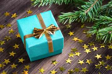 Christmas gift with stars and fir branch twig on wooden table