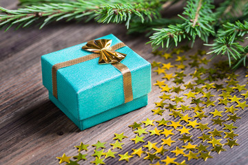 Christmas gift with stars and fir twig on wooden table