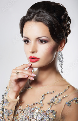 Portrait of elegant woman with evening hairstyle and earrings.