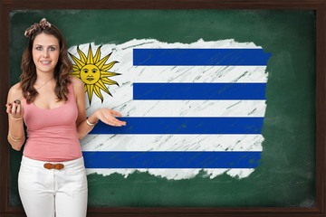 Beautiful and smiling woman showing flag of Uruguay on blackboar