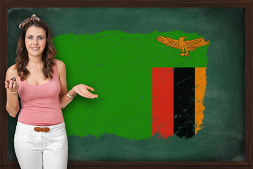 Beautiful and smiling woman showing flag of Zambia on blackboard