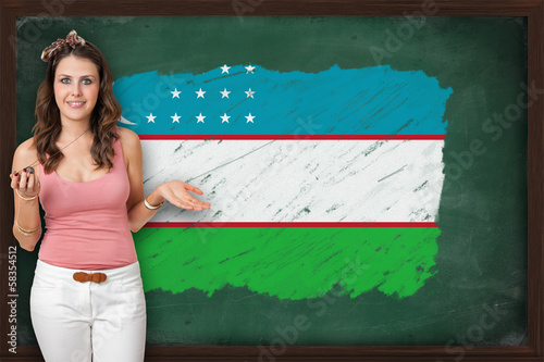 Beautiful and smiling woman showing flag of Uzbekistan on blackb