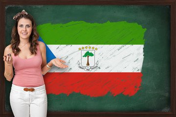 Beautiful and smiling woman showing flag of Equatorial Guinea on