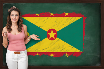 Beautiful and smiling woman showing flag of Grenada on blackboar