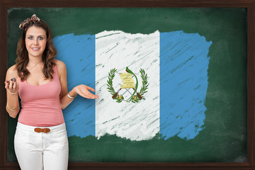 Beautiful and smiling woman showing flag of Guatemala on blackbo