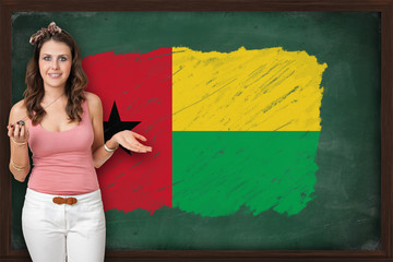 Beautiful and smiling woman showing flag of Guinea on blackboard