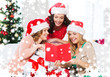 women in santa helper hats with card and gifts
