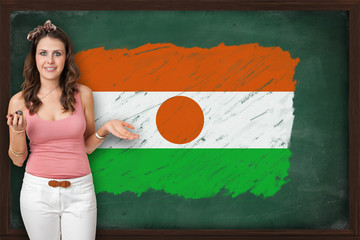 Beautiful and smiling woman showing flag of Niger on blackboard