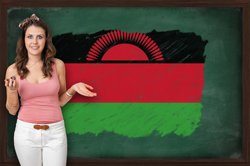 Beautiful and smiling woman showing flag of Malawi on blackboard