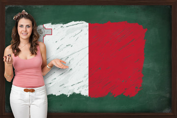 Beautiful and smiling woman showing flag of Malta on blackboard