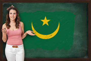 Beautiful and smiling woman showing flag of Mauritania on blackb
