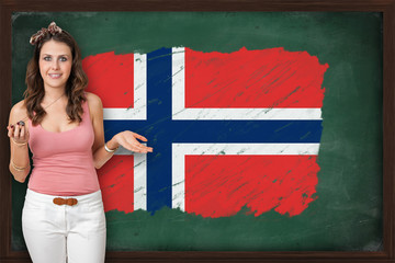 Beautiful and smiling woman showing flag of Norway on blackboard