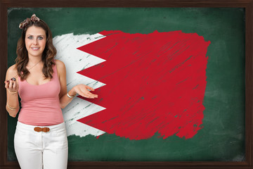 Beautiful and smiling woman showing flag of Bahrain on blackboar