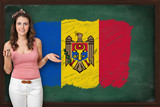 Beautiful and smiling woman showing flag of Moldova on blackboar