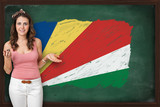 Beautiful and smiling woman showing flag of Seychelles on blackb