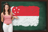 Beautiful and smiling woman showing flag of Singapore on blackbo