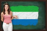 Beautiful and smiling woman showing flag of Sierra Leone on blac