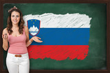 Beautiful and smiling woman showing flag of Slovenia on blackboa
