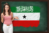 Beautiful and smiling woman showing flag of Somaliland on blackb
