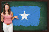 Beautiful and smiling woman showing flag of Somalia on blackboar