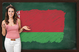 Beautiful and smiling woman showing flag of Belarus on blackboar