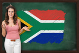 Beautiful and smiling woman showing flag of South Africa on blac