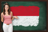 Beautiful and smiling woman showing flag of Monaco on blackboard