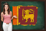 Beautiful and smiling woman showing flag of Sri Lanka on blackbo