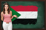 Beautiful and smiling woman showing flag of Sudan on blackboard