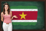 Beautiful and smiling woman showing flag of Suriname on blackboa