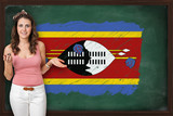 Beautiful and smiling woman showing flag of Swaziland on blackbo