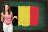 Beautiful and smiling woman showing flag of Belgium on blackboar