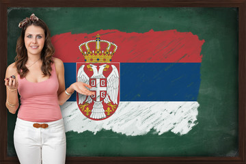 Beautiful and smiling woman showing flag of Serbia on blackboard
