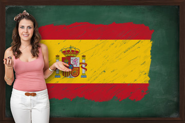 Beautiful and smiling woman showing flag of Spain on blackboard
