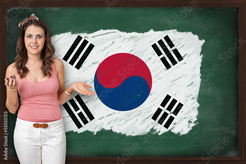 Beautiful and smiling woman showing flag of South Korea on black